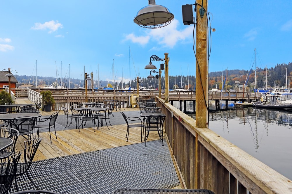 Large deck on water with dining table sets. View of dock and boats. Gig Harbor.